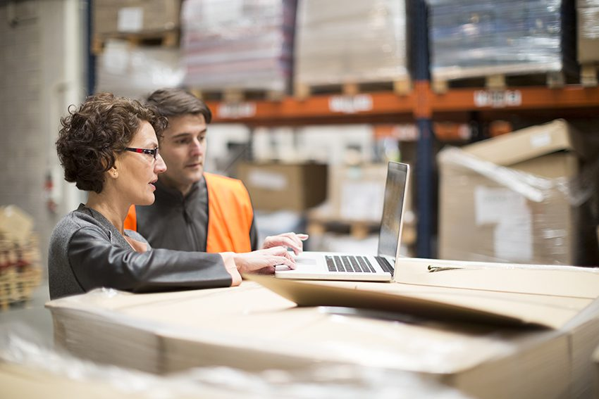 Woman on laptop talking to man in warehouse